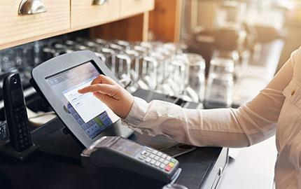 Hand tippt auf Kassensystem mit Touch Kasse
