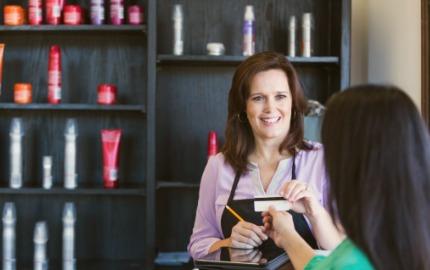 Friseurin mit Kassensystem nimmt Kundenkarte an