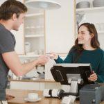 Cafébedienung kassiert Kunde mit Kassensystem