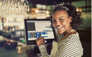 Kasse mit Touchscreen wird von einer jungen Frau bedient