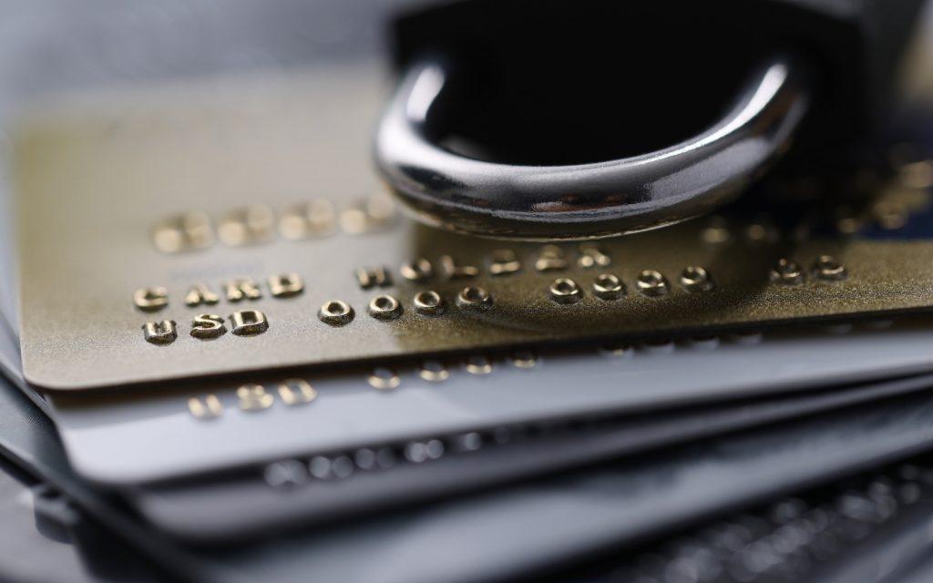Terminal Sicherheit Symbolbild: Mehrere Kreditkarten und ein Vorhängeschloss