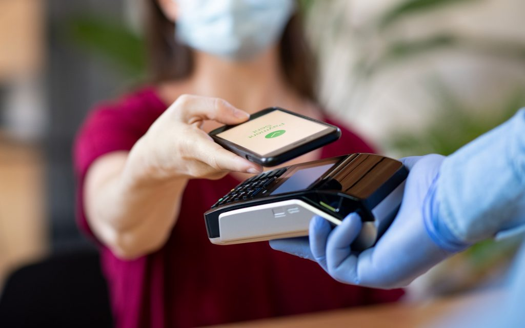 Eine Frau, die ein rotes Oberteil trägt bezahlt mit dem Smartphone an einem NFC Kontaktlos Terminal. Alle Personen im Bild tragen eine Maske.